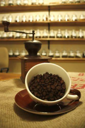 Kaffeebohnen in der Tasse, mit Mühle